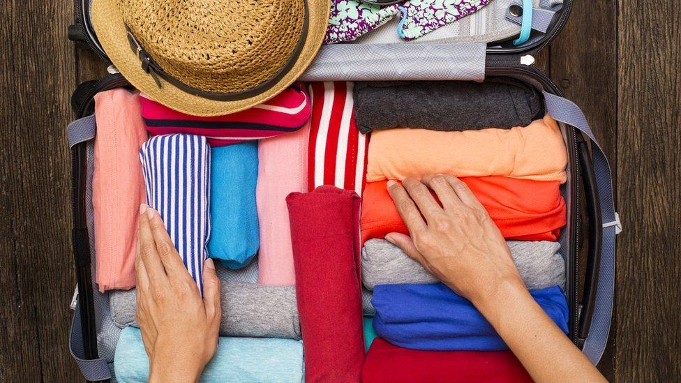 enrolla la ropa en la maleta